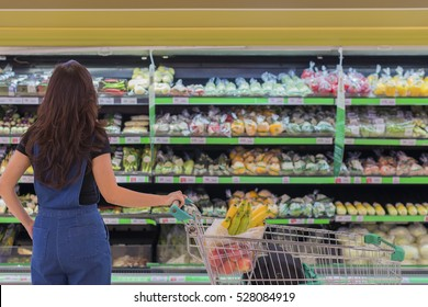Back side of Woman is overwhelmed with the wide range in the supermarket when shopping and Blur abstract background of fruit, vegetable on shelves. (lens blur effect and advertise concept)