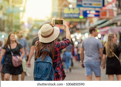 Back side of Young Asian traveling women taking photo in Khaosan Road walking street at night in Bangkok, Thailand, traveler and tourist concept