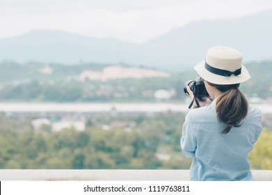 Back side of young Asian traveling woman looking and taking photos of beautiful landscape of Northern Thailand, traveller and tourist concept.