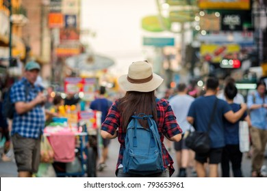 Back side of Young Asian traveling women walking and looking in Khaosan Road walking street in evening at Bangkok, Thailand, traveler and tourist concept