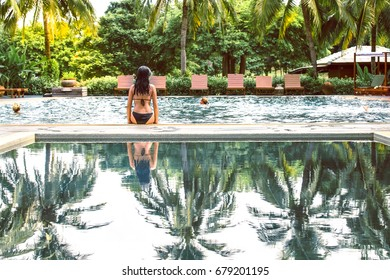 Back side of young girl in black bikini sitting on the edge of the pool with palm trees's reflection. Lifestyle concept