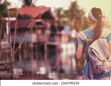 Back side of Young traveling women with backpack in fisherman village are walking in evening at asian, town. Happy female traveler and tourist concept.