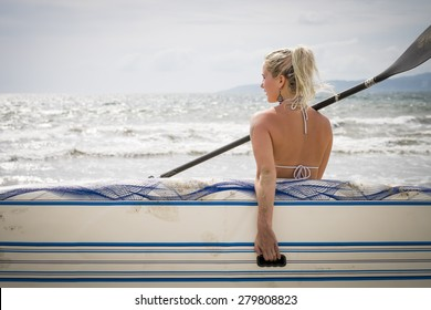 Back side of young woman carrying paddle board, looking at sea. Riviera Nayarit, Pacific Coast, Mexico
