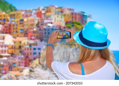 Back side of young woman taking picture of beautiful colorful old Italian buildings, happy travel to Europe, summer vacation concept