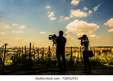 back silhouette of Photographer woman and Videographer man working against blue sky and Prague city town, Czech Republic. wedding time