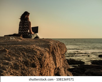 back of a sitting digital nomad woman on a rock at the beach working with her laptop during sunset