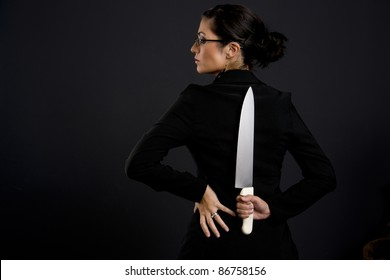 Back Stabber Professional Woman Holds Large Kitchen Knife Blade Behind Her