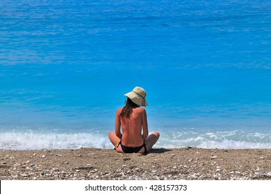Back of sunburned young caucasian woman in a topless swimsuit with a hat, sitting cross-legged at a seashore.