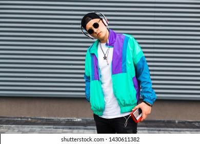 Back in time 90s 80s. Stylish young man in a retro jacket and with a vintage cassette player, on the background of a steel wall, fashion trends, street image