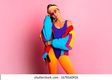 Zurück in den 80ern. Stilvolles Mädchen in Retro-farbigem Vintage-Mantel, orangefarbene Leggings, violetter Körper, Modetrends, Unterhaltung. Mode der 80er Jahre auf rosafarbenem Hintergrund. Schönes athletisches Mädchen.