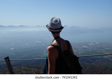 Back of tourist in hat looking out from Mount Vesuvius