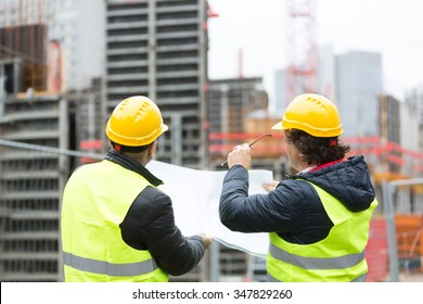 Back turned architect and technician at construction site reviewing office blueprints