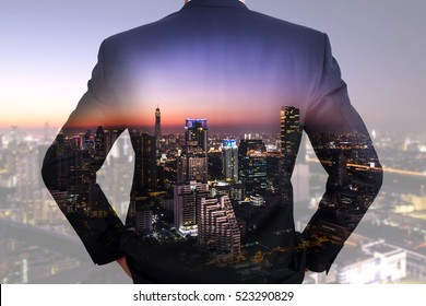 A back turned businessman, cityscape, urban and street in the night as vision of leader concept.