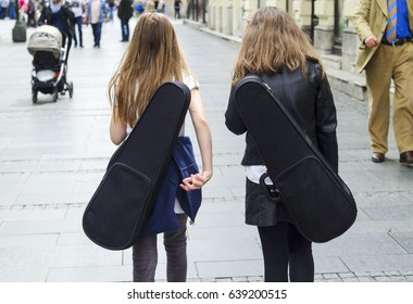 The back of two little girl friend walk together on the street with violin in box.
