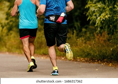 back two male runners run in autumn park on road