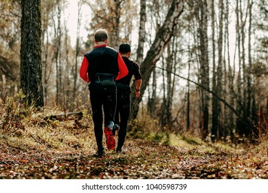 back two male runners running autumn forest trail