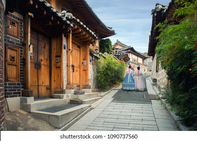 Back of two woman wearing hanbok walking through the traditional style houses of Bukchon Hanok Village in Seoul, South Korea.