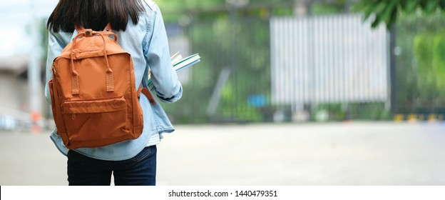 Back of university student with backpack while going to college by walking from street, teenager in campus, education concept