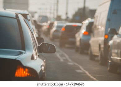 The back of an unknown car at sunset on road in heavy traffic