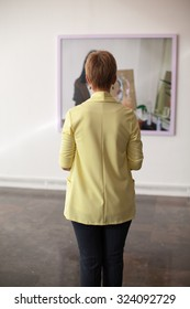 Back unrecognizable woman looking at a painting in a museum