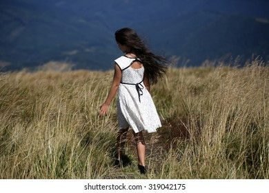 94f95e9c96f2b Back viev of young little brunette girl in white lace summer dress standing  in mountain valley
