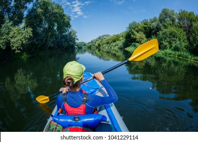 Back view of Active Girl with having fun and enjoying adventurous experience kayaking on the river on a sunny day during summer vacation
