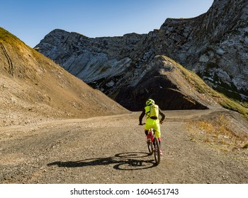 Back view of active sport man riding mountain bike at ridge background