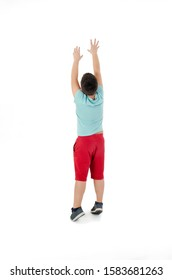 Back view of adorable boy trying to catch something, isolated on white background