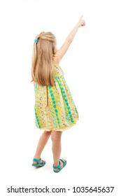 Back view of adorable little girl pointing at wall. Rear view. Isolated on white background