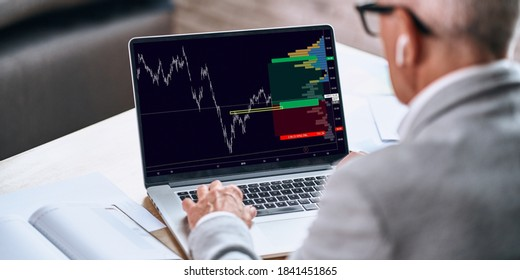 Back view of adult man using in wireless headphones and analyzing stock market data while sitting in the office. Business concept