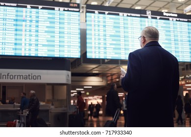 Back view of adult man wearing black coat, holding tickets and passport in hand, checking flight timetable in international airport - business travel without delays concept
