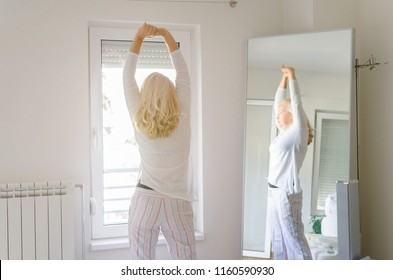 Back view of adult woman stretching after waking up on morning.