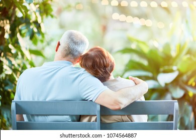 Back view of affectionate senior spouses having rest on bench in natural environment