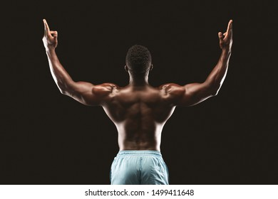 Back view of african american bodybuilder raising his hands up, showing gun gesture, black studio background