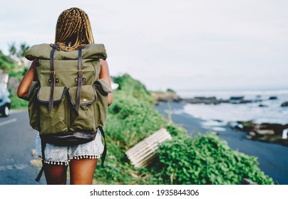 Back view of African American female tourist with backpack exploring nature environment during summer adventure on tropical island, dark skinned active woman with touristic rucksack outdoors