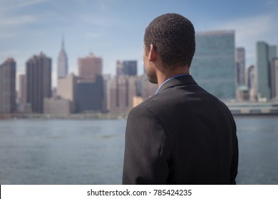 Back view of African American male professional in suits standing across New York City skyline and contemplating, photographed in September