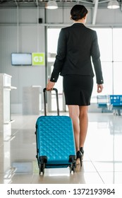 back view of african american stewardess walking with suitcase in airport
