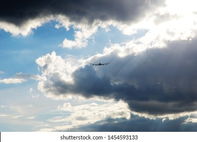 Back view of airplane silhouette flying away against clear blue sky gap between dramatic heavy clouds in rays of sun. Freedom, vacation, runaway and air travel concept