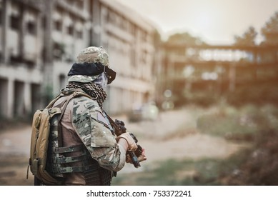 Back view of alone soldier with submachine-gun in Central War building background