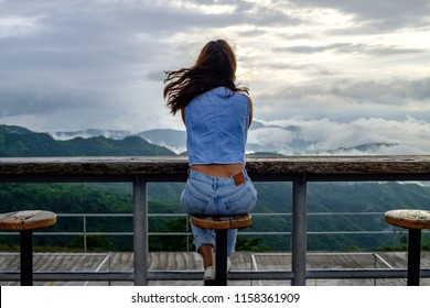 Back view ,Alone traveller asian woman on blue jeans looking towards out of mountain and fog ,Khao kho Phetchabun, Thailand