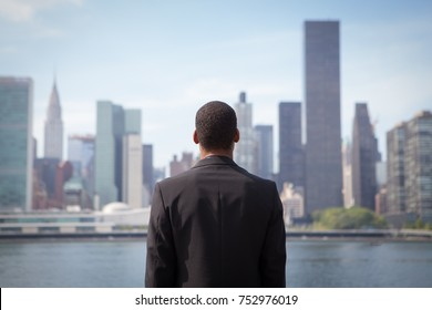 Back view of ambitious young African American business man looking at NYC skyline, photographed in NYC in September
