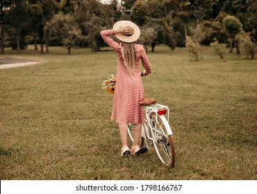 Back view of anonymous female in dotted dress and hat standing on green lawn near bicycle on summer day in park