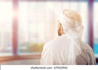 back view of Arab business man wearing kandura and ghutra looking away for success and proud of him self. Business arab concept