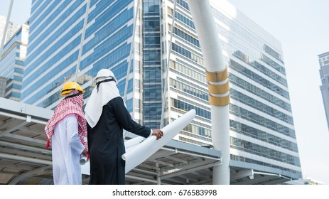Back view of Arabic engineer and Arab businessman checking construction, hand holding  blueprint at construction site with city background.