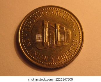 Back view of Argentinian coin. 50 centavos from Argentina. Great for numismatic collection. Shiny coin isolated on yellow surface of paper.