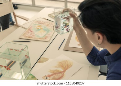 back view of artist watching fish in fish tank to draw or sketch fish in craft paper on table