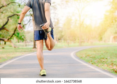 Back view of Asia man runner doing stretching exercise, warm up before for running in morning on track in the park  - Shutterstock ID 1662738568