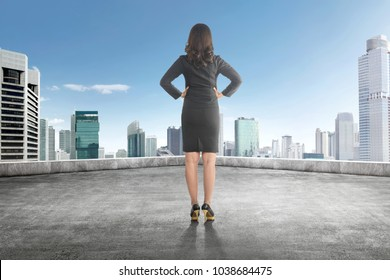 Back view of asian business woman with hand on her waist on the rooftop looking at blue sky