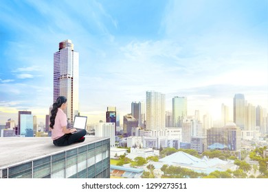 Back view of asian business woman working with laptop on the rooftop