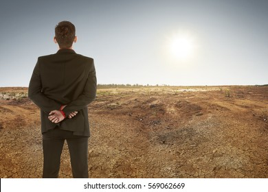 Back view of asian businessman on dry ground and sunset. Climate change concept